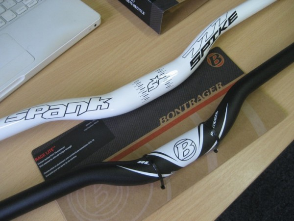 """Two handlebars. The white one is a """"777 Spike"""" from Spank (777mm wide). The black one is a Bontrager """"Race Lite"""" (650mm)."""